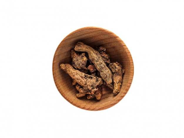Kalgana-wurzel in einer hölzernen schale auf einer weißen tabelle