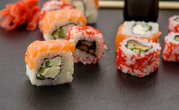 Kalifornien-sushi mit rotem tobiko-kaviar und scheiben von philadelphia-sushi auf schwarzem schieferbrett, draufsicht