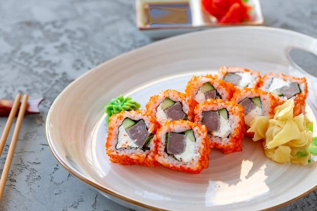 Kalifornische rolle mit japanischer küche des thunfischs in der platte auf grauem tisch