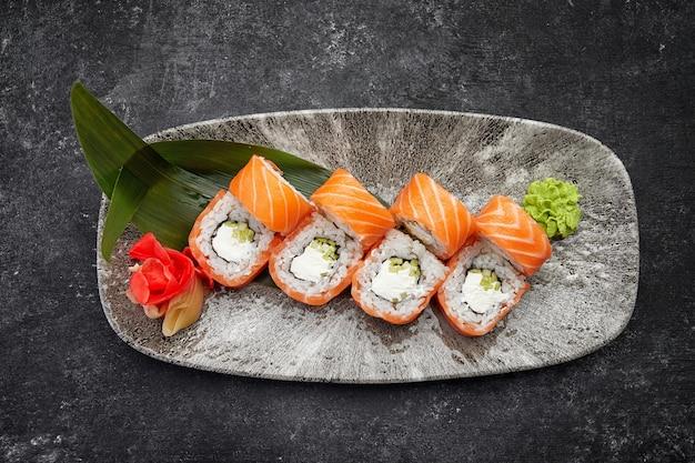 Kalifornische sushi-rolle mit gurken-avocado-frischkäse und lachs auf einem grauen teller auf einem dunklen tisch