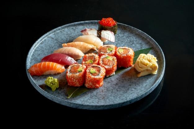 Kalifornische sushi-rolle mit lachs in tobiko-kaviar und verschiedenen sushi. sushi mit lachs, thunfisch, garnelen