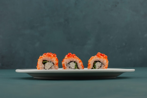 Kalifornische sushirolle mit kaviar auf blauem tisch.