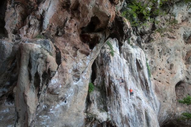 Kalksteinmauer mit touristenklettern in der provinz krabi in thailand.