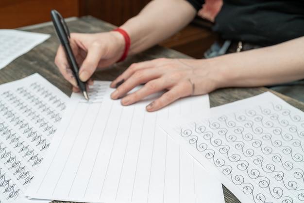 Kalligraphie-ausbildung. füllfederhalter in tintenfleckigen händen.