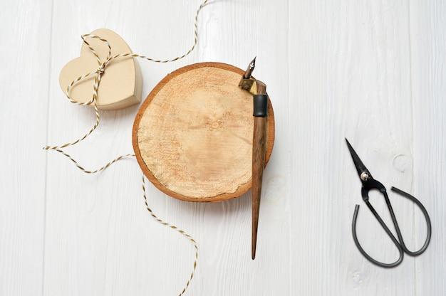 Kalligraphische feder, liegt nahe einem hölzernen kreis mit einem weißbuchherzen. grußkarte zum valentinstag