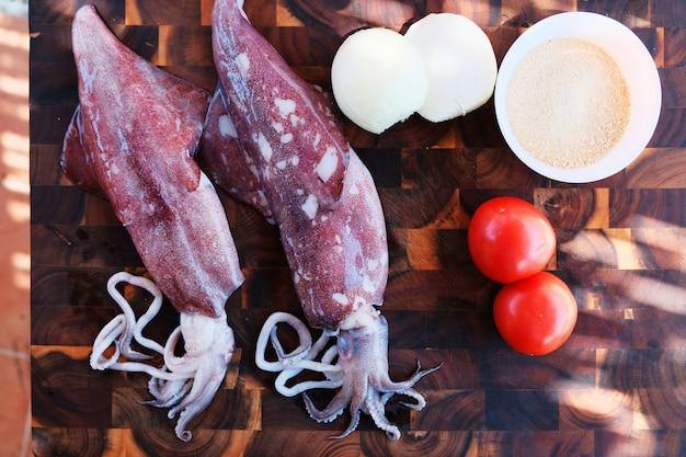 Kalmare mit gemüse auf hölzernem hintergrund