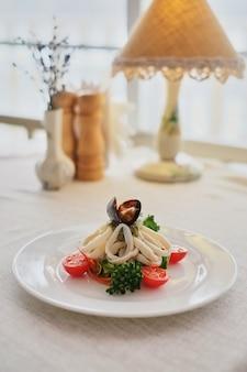 Kalmare und miesmuscheln mit gemüse auf einer weißen platte auf einem weißen hintergrund