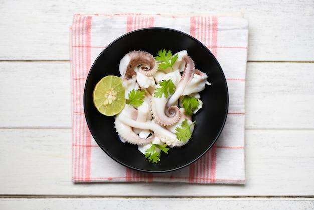 Kalmarsalatschüssel mit zitronenkräutern und -gewürzen auf holzoberfläche