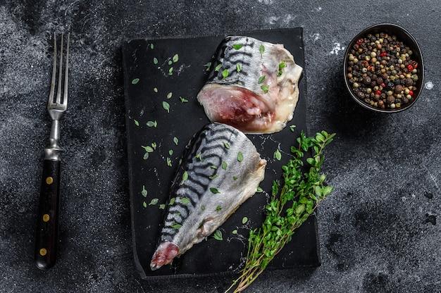 Kalt geräucherter makrelenfisch mit kräutern. schwarzer hintergrund. ansicht von oben.