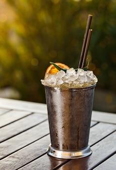 Kalte cocktailgetränke in einem einzigartigen mit frisch geschnittenem orangefarbenem und grünem chili.