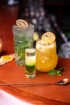 Kalte cocktails mit limettenminze und eis in einem glas mit tropfen alkoholgetränk an der bar