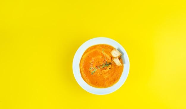 Kalte cremesuppe gazpacho auf einem gelben tisch köcheln lassen