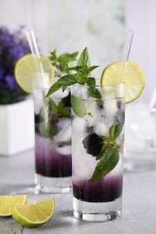 Kalte erfrischung alkoholfreier bio-cocktail brombeer-mojito mit beerenfrucht im glas