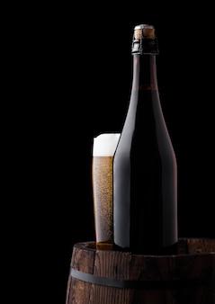 Kalte flasche und glas handwerksbier auf altem hölzernem fass auf schwarzem hintergrund