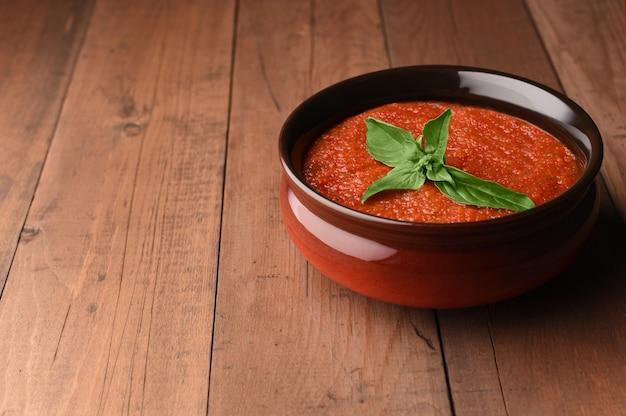 Kalte gazpacho-suppe der spanischen tomate in der schüssel mit basilikum. hausgemachte gazpacho von roten tomaten zubereitet.