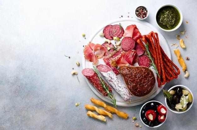 Kalte geräucherte fleischplatte. traditioneller italienischer antipasto, schneidebrett mit salami, prosciutto, schinken, schweinekoteletts, oliven auf grau. draufsicht, textfreiraum, flach legen
