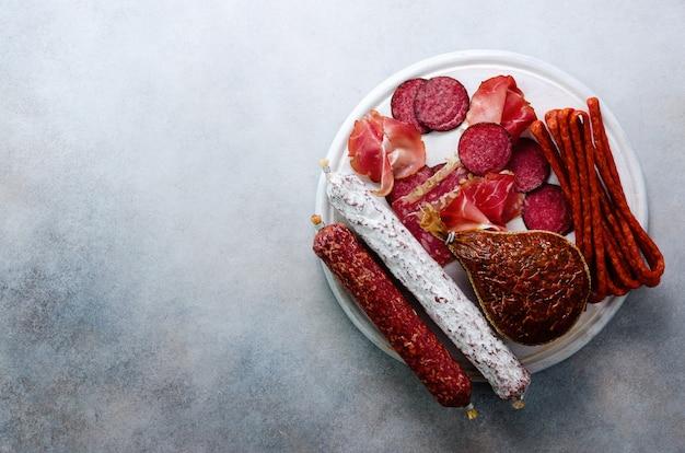 Kalte geräucherte fleischplatte. traditioneller italienischer antipasto, schneidebrett mit salami, prosciutto, schinken, schweinekoteletts, oliven auf grau.