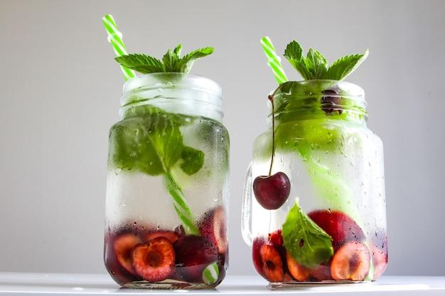 Kalte getränke in kleinen flaschen kirschen und minze limonade mojito-cocktail sommer-eisgetränk