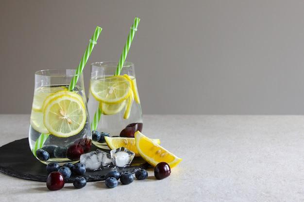 Kalte getränke in kleinen flaschen kirschen und zitronenlimonade mojito-cocktail sommer-eisgetränk