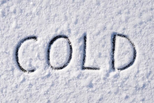 Kalte inschrift auf schneebedeckter oberfläche mit frostmustern