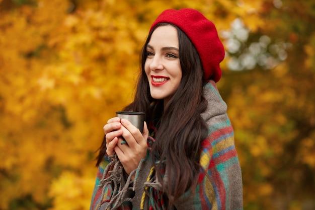 Kalte jahreszeit, heiße getränke und menschenkonzept. außenporträt der schönen glücklichen jungen frau, die rote baskenmütze trägt