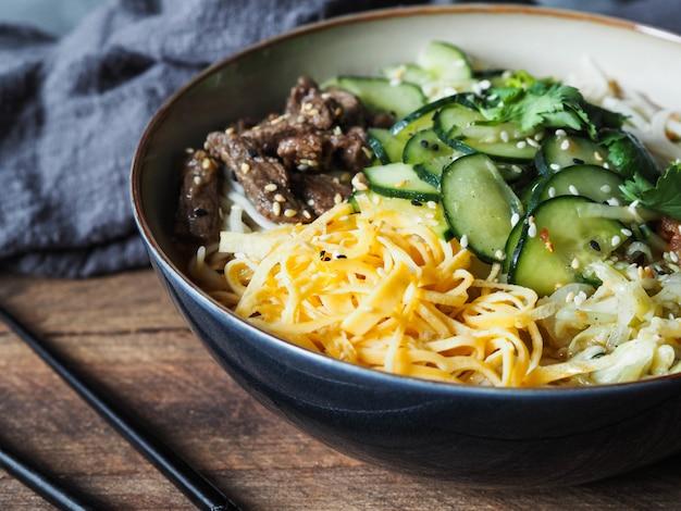 Kalte koreanische kuksi-suppe mit gemüse, rührei, rindfleisch und nudeln in einer schüssel und stäbchen