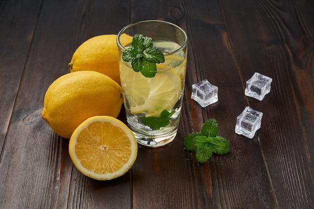 Kalte limonade mit eis auf einem dunklen holz
