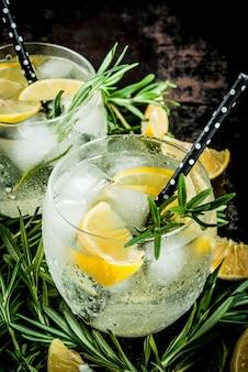 Kalte limonade oder alkohol wodka cocktail mit zitrone und rosmarin, auf einem schwarzen rostigen metallic,