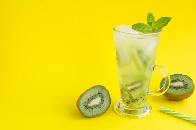 Kalte limonade oder aufgegossenes wasser mit kiwi im glas auf der gelben oberfläche. speicherplatz kopieren.