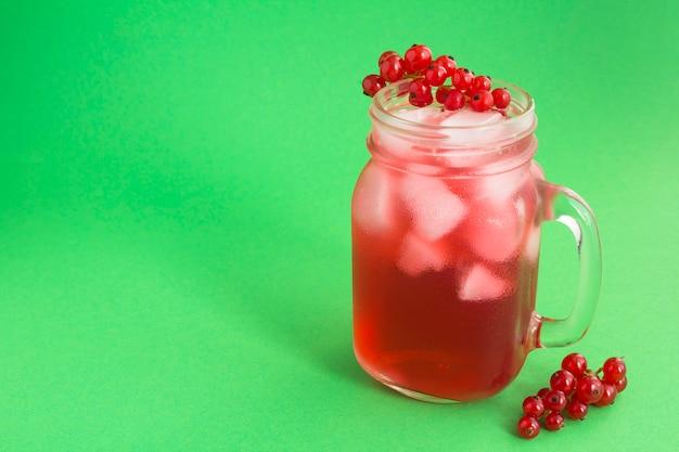Kalte limonade oder cocktail mit roten johannisbeeren im glas auf der grünen oberfläche. nahansicht. speicherplatz kopieren.