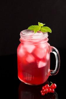 Kalte limonade oder cocktail mit roten johannisbeeren im glas auf der schwarzen oberfläche. nahansicht. lage vertikal.
