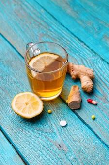 Kalte medikamente, tee, zitrone und ingwer auf holzblau
