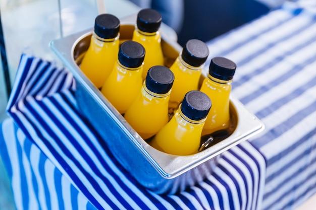 Kalte orangensaftflaschen im aluminiumkasten auf weißem und blauem streifengewebe.