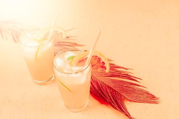 Kalte pampelmuse und orange cocktail in zwei gläsern mit eiswürfeln auf farbigem hintergrund