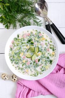Kalte sommersuppe okroshka. leichte suppe in einer weißen schüssel. draufsicht.