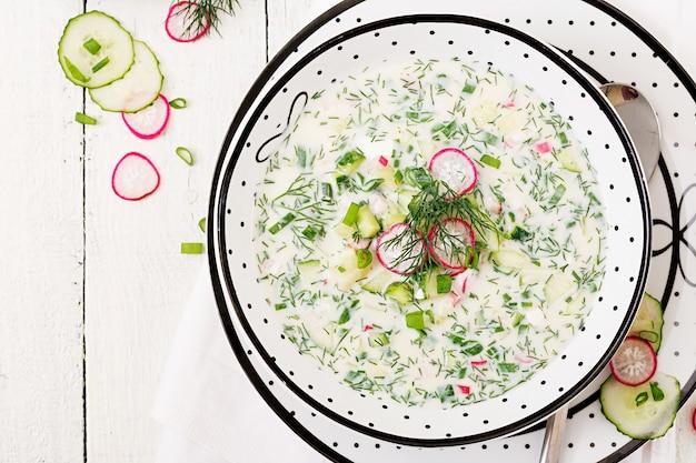 Kalte suppe mit frischen gurken, rettiche mit jogurt in der schüssel auf holztisch. traditionelles russisches essen - okroschka. vegetarische mahlzeit. ansicht von oben. flach liegen