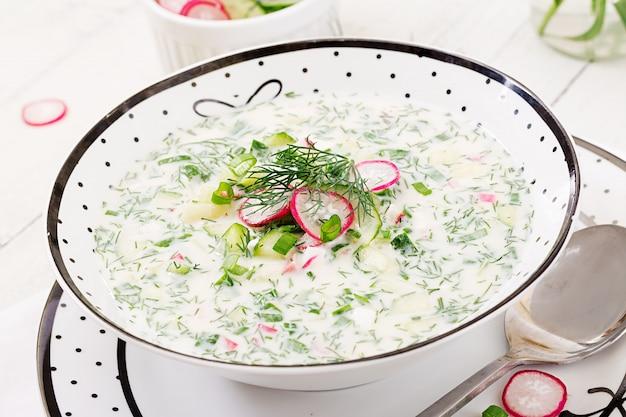 Kalte suppe mit frischen gurken, rettiche mit jogurt in der schüssel auf holztisch. traditionelles russisches essen - okroschka. vegetarische mahlzeit.