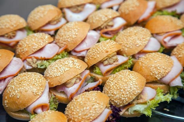 Kalte vorspeisen auf einem tablett. hamburger mit speck und kräutern in mehreren reihen