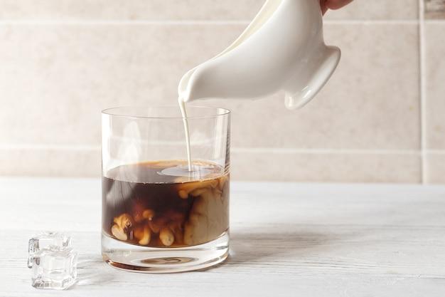 Kalten kaffee kochen, sahne zum eiskaffee geben