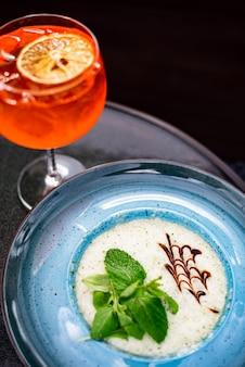 Kalter aperol spritz zitruscocktail mit orangensaft und limettenminze und eis in einem glas an der bar