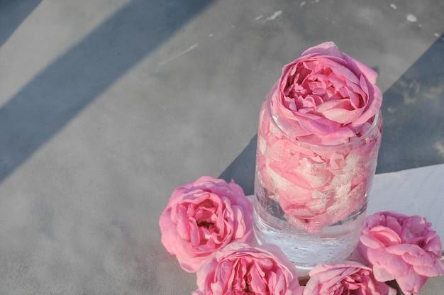 Kalter cocktail aus rosa teerosenblättern in einem glasglas auf grauem hintergrund mit rosenblüten