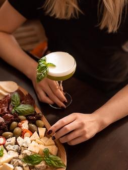 Kalter cocktail mit limettenminze und eis in einem glas mit tropfen alkoholgetränk an der bar