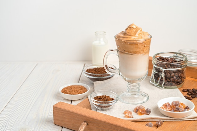 Kalter dalgona-kaffee auf einem braunen tablett mit zutaten. seitenansicht, kopienraum.