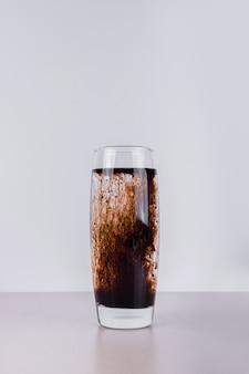Kalter dunkler cocktail auf weiß