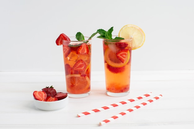 Kalter erdbeer-limonadensaft mit eiswürfeln, minze, zitrone, cocktail-röhre und auf weißem hintergrund. kaltes sommergetränk.