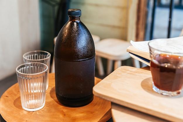 Kalter espressokaffee innerhalb der schwarzen flasche auf holztisch mit leeren trinkgläsern.