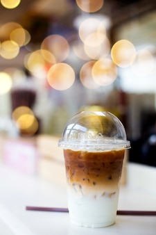 Kalter kaffee in der plastikschale auf einem holztisch im café