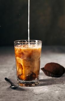 Kalter kaffee in einem hohen glas mit milch- und schokoladenkeksen an einer grauen dunklen wand mit kopienraum milch wird in kaffee gegossen