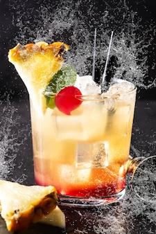 Kalter mai tai cocktail im glasspritzer auf schwarzem stein