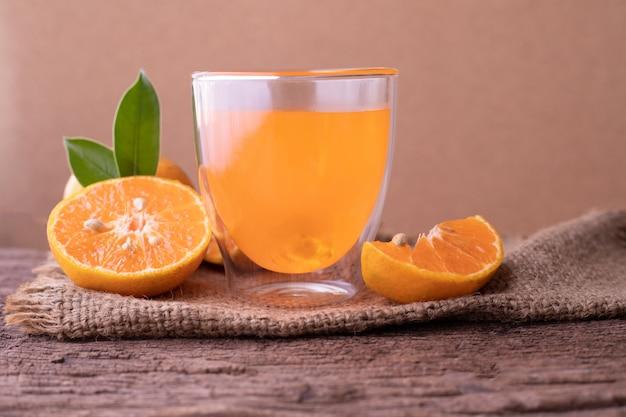 Kalter orangensaft und geschnittene orange auf hölzerner tabelle.